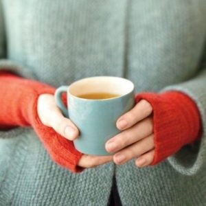 Womens hands holding a cup to keep warm